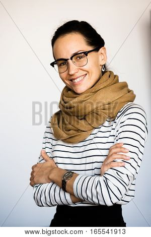 Portrait of businesswoman posing with scarf on with her arms crossed or folded in studio. Business lady in glasses happy smiling for camera. Open wide diaphragm concept.