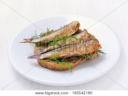 Fish sandwich with sprats on a white plate