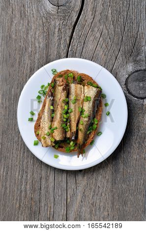 Fish sandwich with sprats on wooden table top view