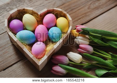 Happy Easter - colored tulips and eggs in a heart shaped bowl on a wooden background