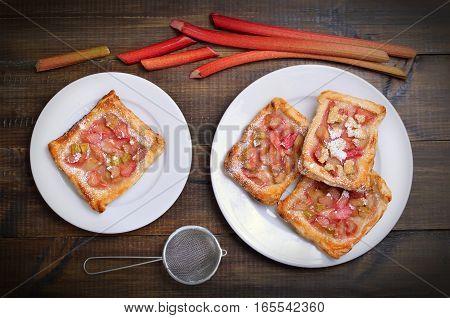 Rhubarb pie on white plate and fresh rhubarb top view