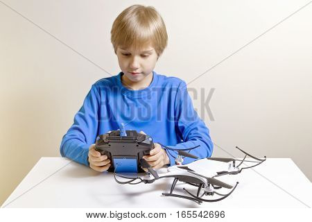 Little kid is going to play with the quadcopter drone at home. Boy holding a radio remote control. Technology, education, leisure, toys concept