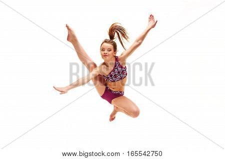 The teenager girl doing gymnastics exercises and jumping on a white background