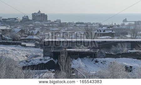 The snow-covered factory and the city on a winter morning