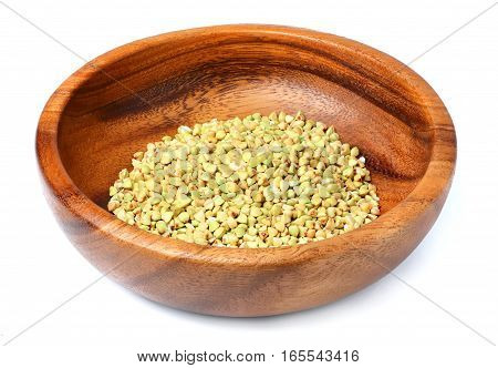 Wooden bowl with of green buckwheat isolated on white background.