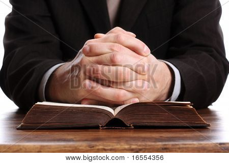 Hands folded in prayer on an open bible poster