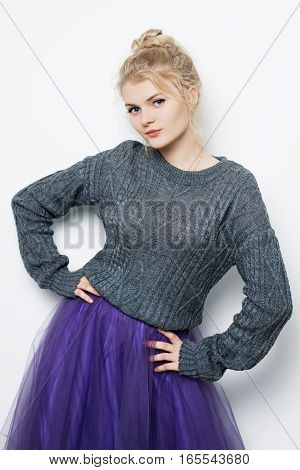 beautiful blonde girl posing in a sweater in the studio on a white background