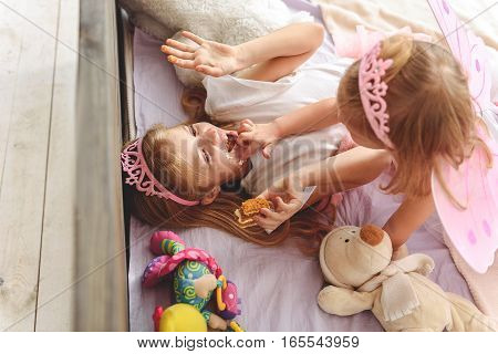 Eat this tasty cake. Top view of pretty girl putting cream on her elder sister face. She is lying on bed and laughing