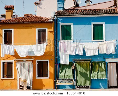 Laundry hanging from colorful buildings in Burano island Venice Veneto Italy
