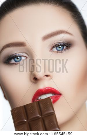 attractive brunette woman with red lipstick eats chocolate on white background