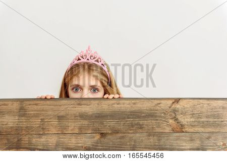 Scared girl is hiding behind wooden fence and staring at camera with fear. She is wearing pink crown. Isolated