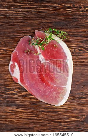 Raw gammon steak on wooden background with thyme.