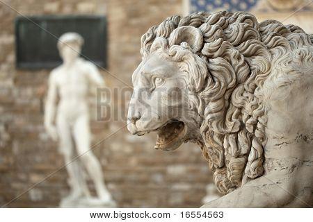 Statue of a lion at the Loggia dei Lanzi in Piazza della Signoria in Florence Tuscany. Michelangelo's David statue in front of the Palazzo Vecchio background poster