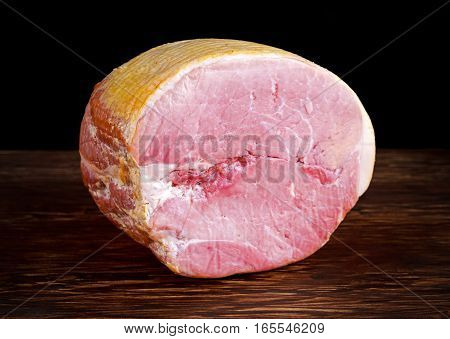 Butcher's deli ham on wooden board background.