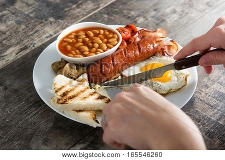Woman eating a traditional English breakfast with fried eggs, sausages, beans, mushrooms, grilled tomatoes, bacon, coffee and orange juice, on wooden table