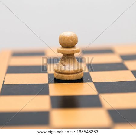 Vintage wooden chess pawn on the chess board closeup