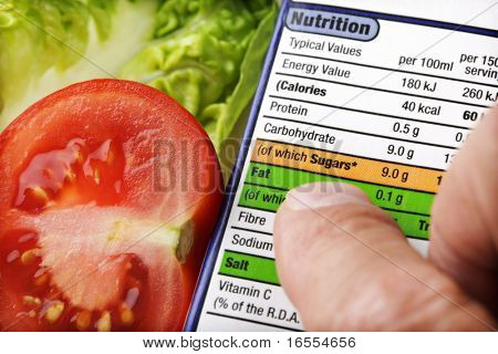 Reading a nutrition label on food packaging with fresh salad background