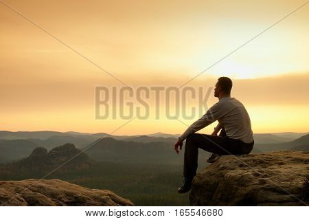Hiker In Black Sit Alone On Summit. Wonderful Mountains
