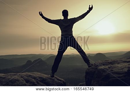 Happy man with raised arms gesture triumph on exposed cliff. Satisfy hiker silhouette on sandstone cliff watching down to hilly landscape.