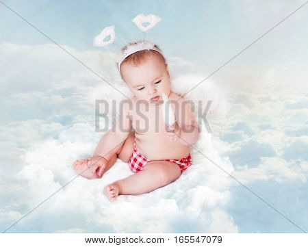 Baby Newborn with Angel Wings and feather. Child Sitting at Blue Sky Cloud. Artistic Fantasy Sky Background. .