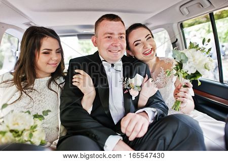 Happy smiled groom sitting on wedding car with bridesmaids.