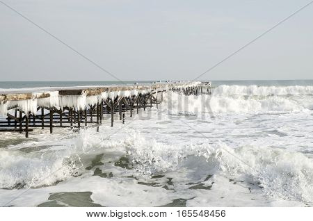 Old icy pier with icicles in winter in stormy sea