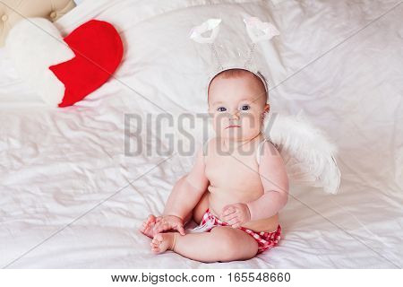 Baby with angel wings. Child Sitting at white blanket near the heart shaped pillow