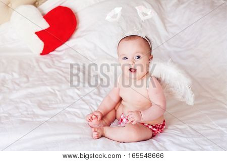 Baby with angel wings. Child Sitting at white blanket