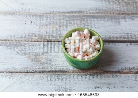 Marshmallows in plate on white wood rustic table background. Toned image with copy space for text