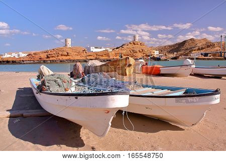 SUR, OMAN - FEBRUARY 7, 2012: Fishing boats in Ayjah, Sur with watch towers in background