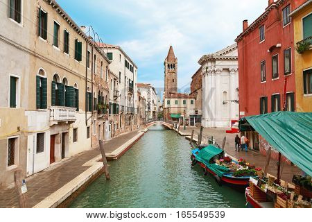 Italy. The cityscape and architecture of Venice. Urban canal. In the background the bell tower of the church of St. Barnaba