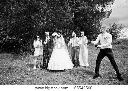 Wedding Couple With Their Friends Drinking Champagne. Black And White Photo