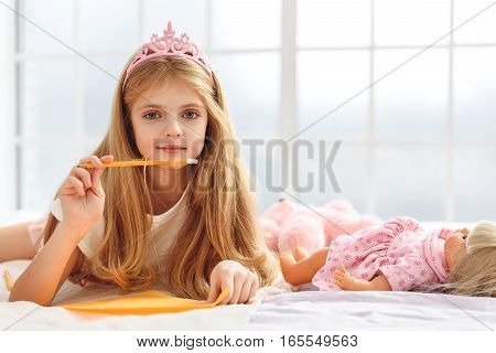 Now I will write the letter to my prince. Happy princess is holding pencil with paper and dreaming. Child is lying on bedding and smiling