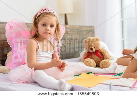 Cute little girl is drawing at home with interest. She is sitting on bed near paper and holding felt-tip pen. Her sister is lying near her
