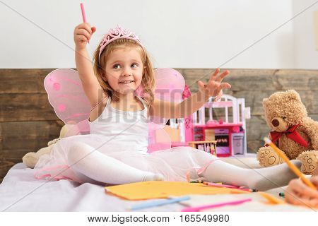 Happy little fairy is holding felt pen and waving it as magic wand. She is sitting on bed and smiling. Girl is wearing pink wings and crown