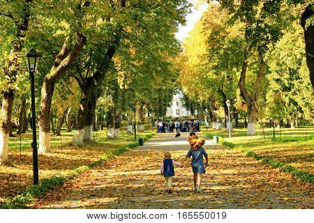 young happy sisters with cries wow run in the autumnal park
