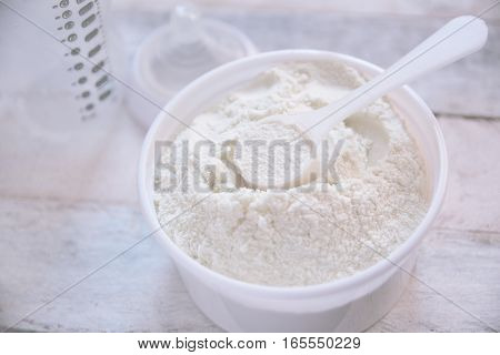 Some milk powder served with a scoop while preparing a baby bottle. Empty copy space for editor's text.