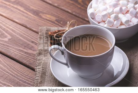 Cup of hot coffee or cocoa and plate with marshmallows on wooden table. Copy space for text