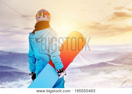 Girl snowboarder stands with snowboard on mountain's top on sunrise backdrop. Sheregesh ski resort