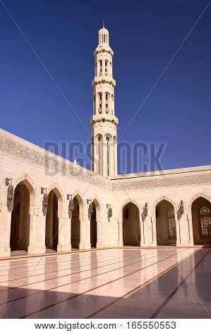 MUSCAT, OMAN: Minaret and courtyard with arcades at Sultan Qaboos Grand Mosque