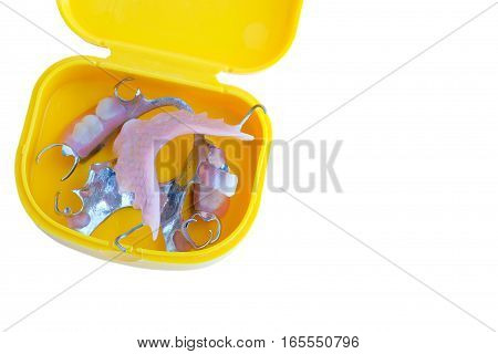 partial dental prosthetics (denture) in yellow case isolated on a white background