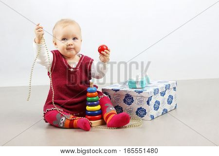 Holidays, Birthday, Children and people concept.Shot of a little adorable baby girl in red dress opening presents and playing toys.