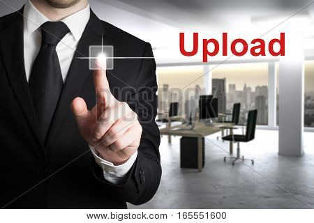 businessman in large modern office pushing button upload