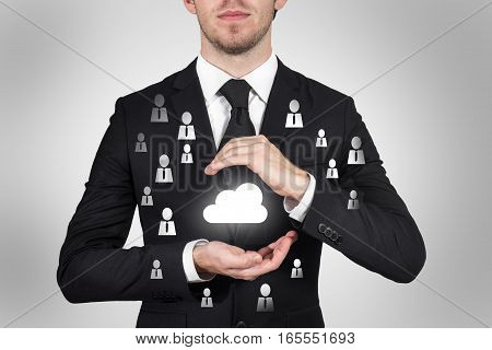 businessman protecting cloud symbol with hands internet community