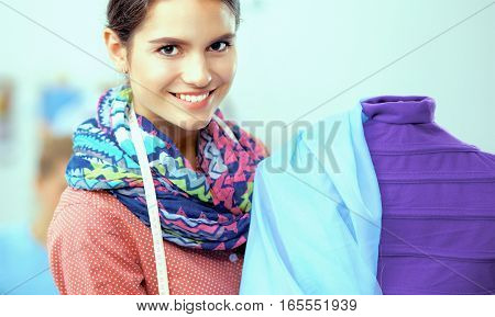 Smiling fashion designer standing near mannequin in office.