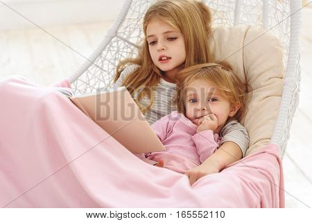 Cute little girl is listening to fairy tale by her sister. They are relaxing on hammock and embracing with love