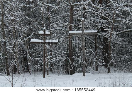 two crosses catholic and orthodox symbols of  union in believe and god bless stay in winter field near road