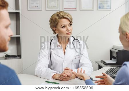Attentive female medico is sitting near table with stethoscope in front of patients. She carefully listening to clients