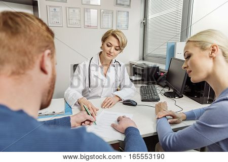 Attentive doctor is sitting in front of patients. She giving special form to man. Woman looking at them