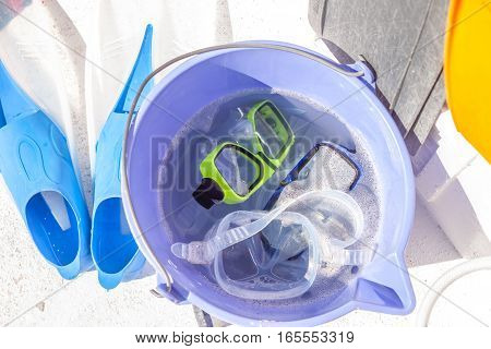 bucket with diving masks and tubes flippers